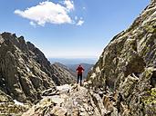 Spain, Sierra de Gredos, hiker standing on rock in mountainscape - LAF001648