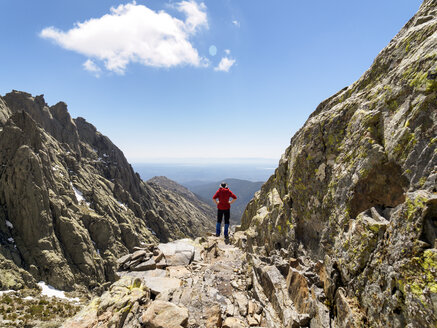 Spain, Sierra de Gredos, hiker standing on rock in mountainscape - LAF001648