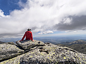 Spain, Sierra de Gredos, hiker sitting on rock in mountainscape - LAF001654
