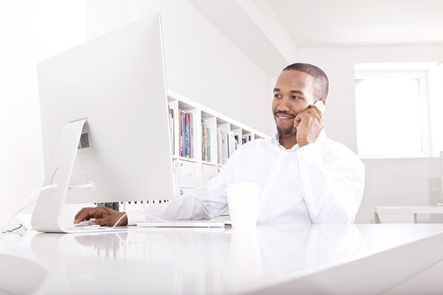 Businessman telephoning at desk in the office - MFRF000621