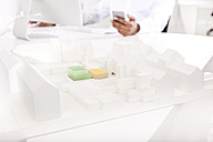 Architectural model on desk with working man in the background - MFRF000627