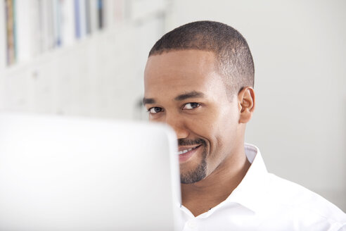 Portrait of smiling man behind his computer - MFRF000633