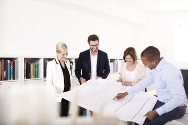 Four colleagues discussing construction plan in an office - MFRF000645