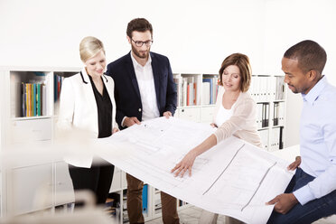 Four colleagues discussing construction plan in an office - MFRF000648