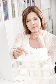 Portrait of woman at desk looking at architectural model - MFRF000663