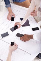 Hands taking smartphones lying on construction plan - MFRF000675