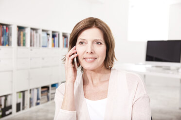 Portrait of woman telephoning with smartphone in the office - MFRF000702