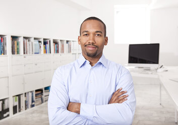 Portrait of businessman with arms crossed in the office - MFRF000705