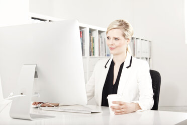 Businesswoman working at desk in the office - MFRF000711