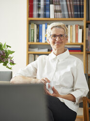 Portrait of smiling senior woman with cup of coffee at home - DISF002484