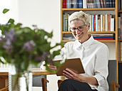 Portrait of smiling senior woman with digital tablet at home - DISF002487