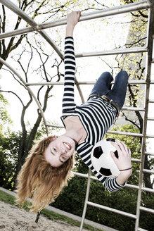 Portrait of smiling girl hanging upside down on jungle gym - JATF000861