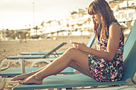 Spain, Tenerife, young woman with smartphone sitting on beach lounger - SIPF000511