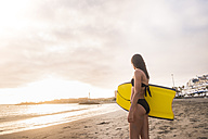 Spain, Tenerife, young woman with swimming board at beach - SIPF000523