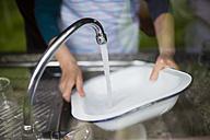 Woman washing dishes at kitchen sink - RAEF001179