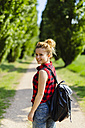 Portrait of smiling woman with backpack in nature - GIOF001131
