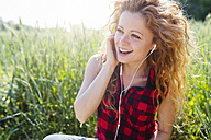 Portrait of woman sitting in a field hearing music with earphones - GIOF001134