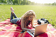 Woman lying on blanket on a meadow using laptop - GIOF001152