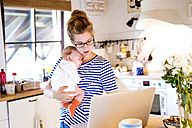 Mother with baby in kitchen looking at laptop - HAPF000467