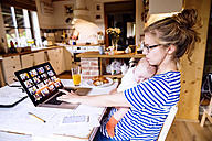 Mother with baby at home working with laptop - HAPF000473