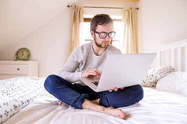 Man sitting on bed using laptop - HAPF000482