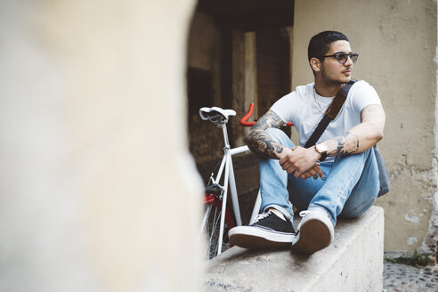 Young man with a bicycle sitting on wall - GIOF001163