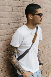 Young man leaning against a brick wall - GIOF001175