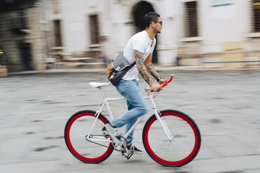 Young man riding bicycle in the city - GIOF001178