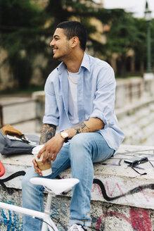 Smiling young man sitting on graffiti wall - GIOF001187