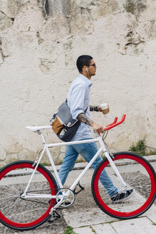 Young man walking with a bicycle in the city - GIOF001190