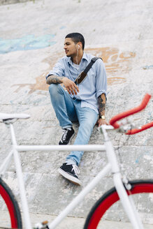 Young man with a bicycle sitting on a wall - GIOF001199