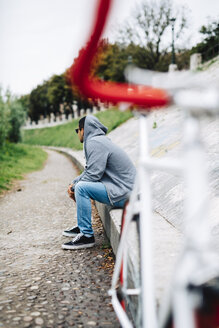 Young man with a bicycle sitting on a wall wearing a hoodie - GIOF001202
