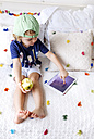 Little boy sitting on the couch with an apple using digital tablet - MGOF001890