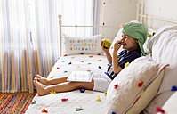 Laughing little boy sitting on the couch with an apple and digital tablet - MGOF001893