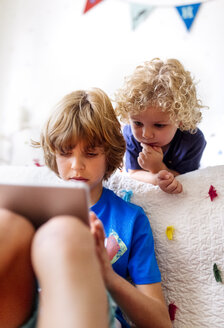 Two little brothers using tablet at home - MGOF001899
