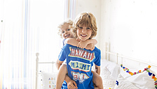 Boy giving his little brother a piggyback ride at home - MGOF001911