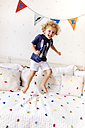 Portrait of laughing little boy jumping on the couch - MGOF001914