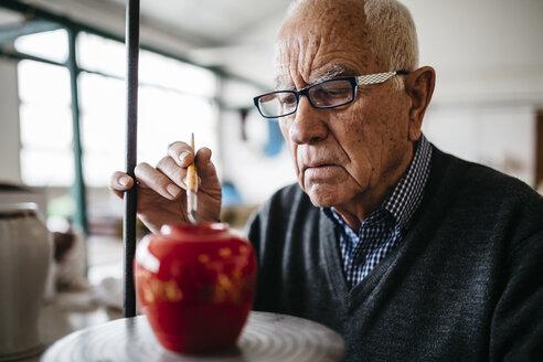 Senior man decorating ceramic vase in his spare time - JRFF000690