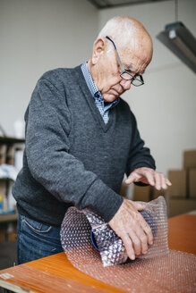 Senior man wrapping the finished ceramic piece - JRFF000696