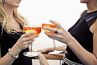 Two women toasting with aperitive, close-up - ONBF000028