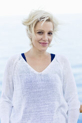 Portrait of smiling blond woman with blowing hair in front of the sea - ONBF000033