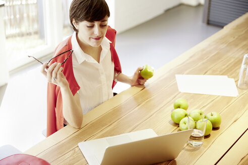 Woman in a modern canteen eating an apple - TSFF000023