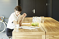 Woman reading newspaper at wooden table in a modern canteen - TSFF000026