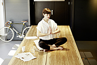 Woman practising yoga on wooden table - TSFF000029
