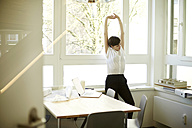 Woman doing stretching exercise in her office - TSFF000050