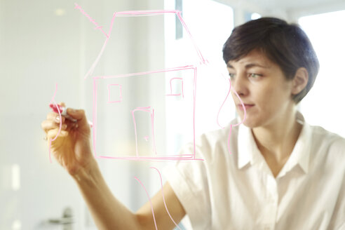 Woman drawing a house on glass pane in an office - TSFF000056