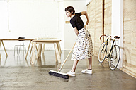 Woman sweeping in a studio - TSFF000062