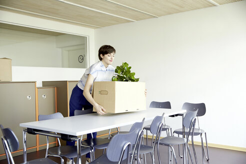 Smiling woman carrying cardboard box in new office - TSFF000077