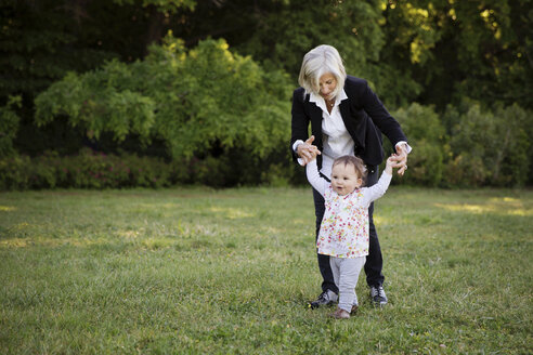 Grandmother helping her little granddaughter walking in the park - LITF000360