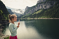 Austria, Gosau, girl with blowball at Gosausee - OPF000114